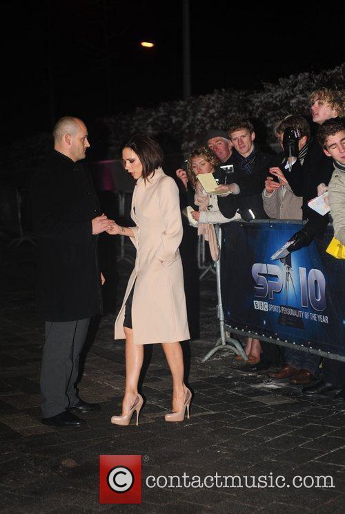 Victoria Beckham hands a pen back to her...