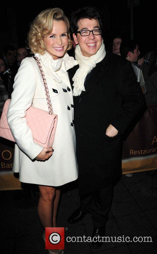 Amanda Holden wearing a white cape coat and...