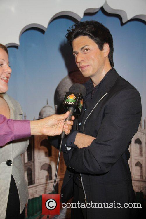 A reporter pretends to interview the wax figure...