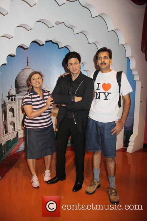 Fans pose with the wax figure of Indian...