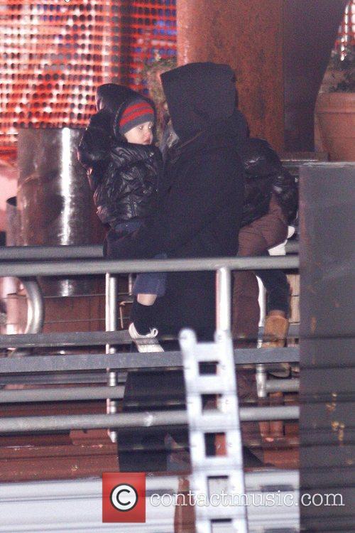 Brad Pitt carries his daughter, Shiloh Jolie-Pitt, as...