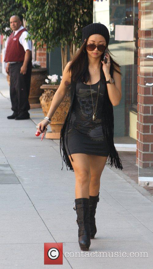 Brenda Song texts from her cell phone outside...