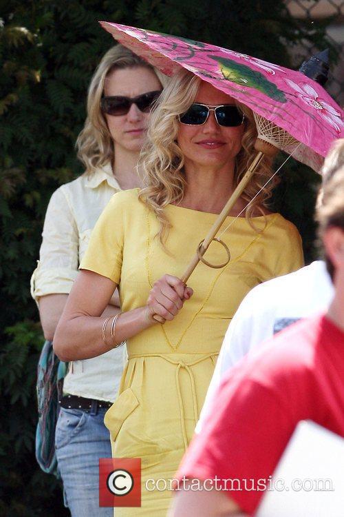 Cameron Diaz holding an umbrella while filming a...