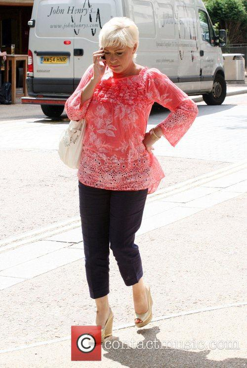 Talks on her mobile phone as she leaves...