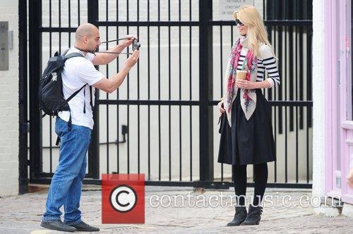 Claudia Schiffer  poses as a fan takes...