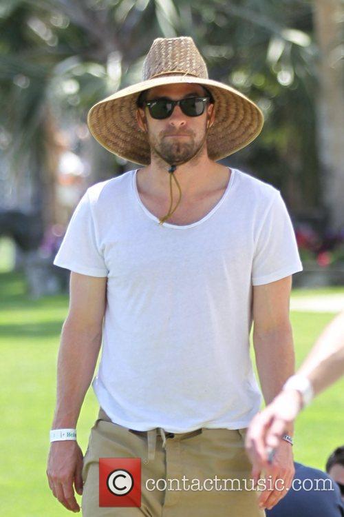 Scott Speedman wearing a wide-brimmed straw hat and...