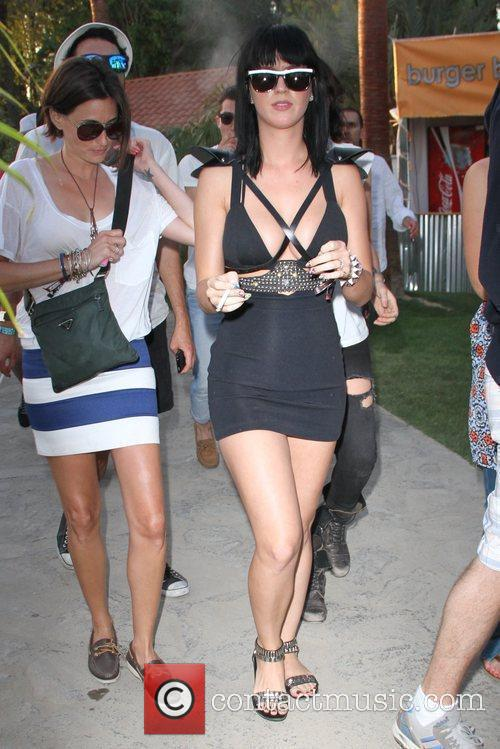 Katy Perry, wearing a form fitting black dress,...