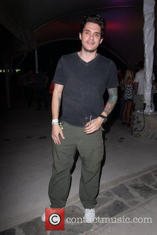 John Mayer holding a drink and posing for...