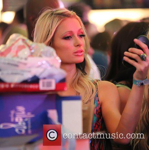 Paris Hilton checks her make-up with a hand...