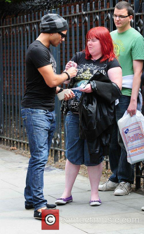 Ryan Thomas stops to sign autographs for fans...