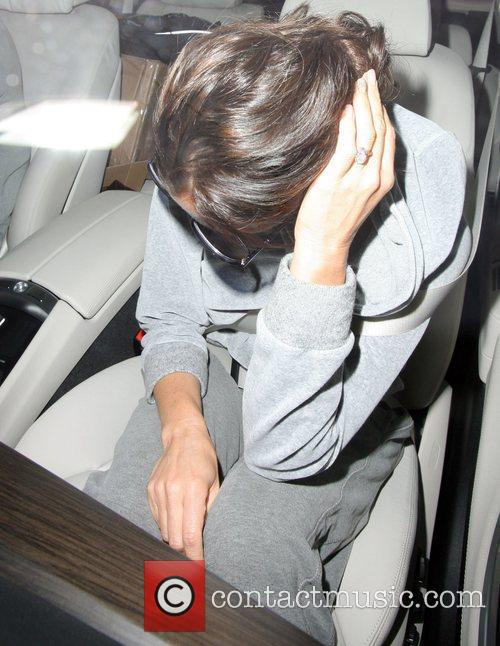 Victoria Beckham hides her face as she gets...