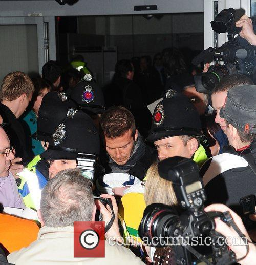David Beckham is mobbed by fans and photographers...