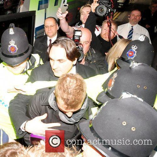 Is mobbed by fans and photographers as he...