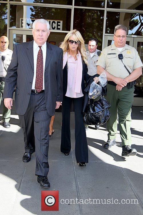 Carrying her daughter Lindsay Lohan's personal belongings as...