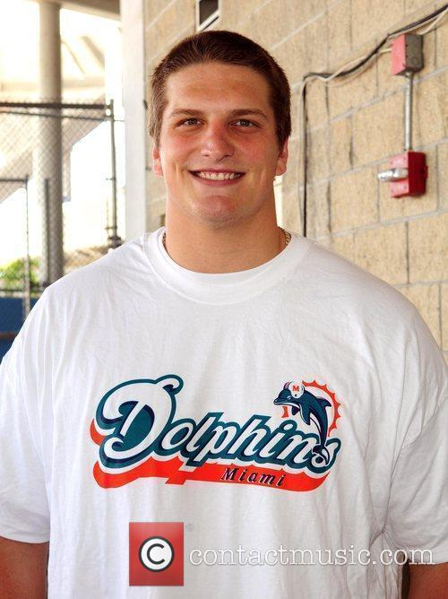Jake Long Miami Dolphins football players distribute meals...