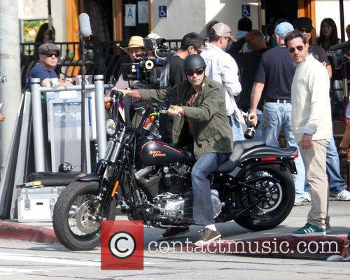 Adrian Grenier riding a Harley-Davidson motorcycle during a...