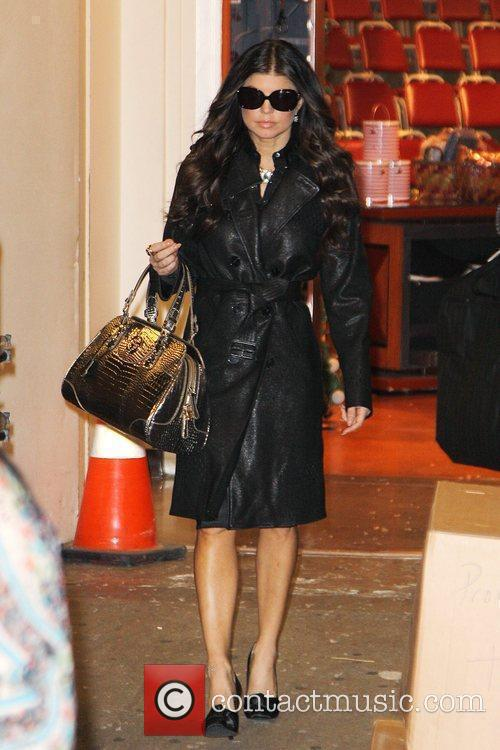 Fergie, aka Stacy Ferguson, sporting black leather trench...
