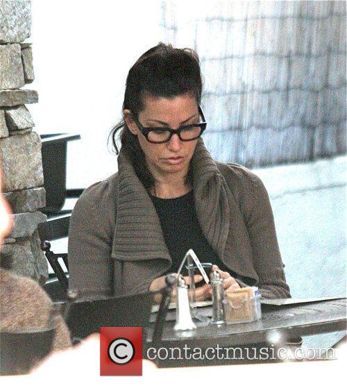 Gina Gershon using her cell phone while having...