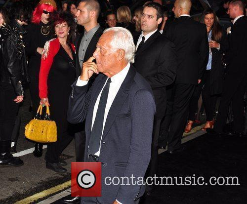 Giorgio Armani appears to be picking his nose,...