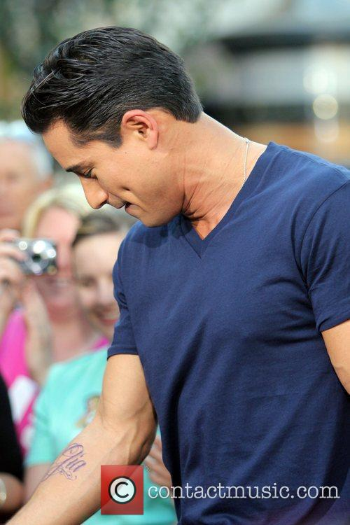 Mario Lopez  shows his tattoo during an...