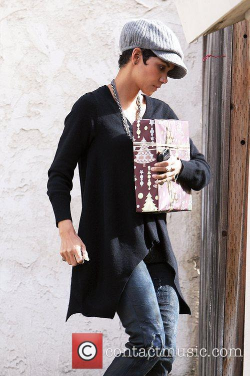 Halle Berry carries a Christmas gift into a...
