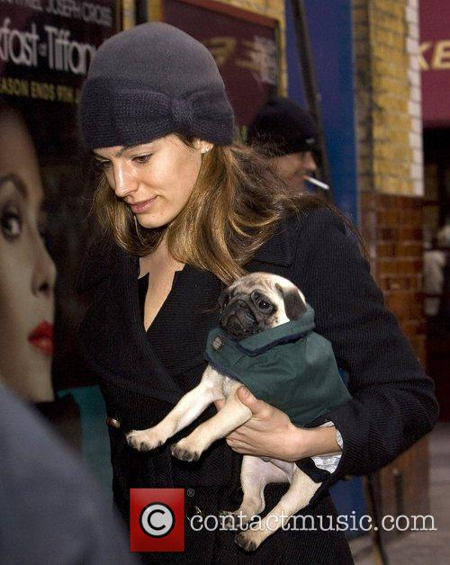 Carries her new Pug puppy Rocky as she...