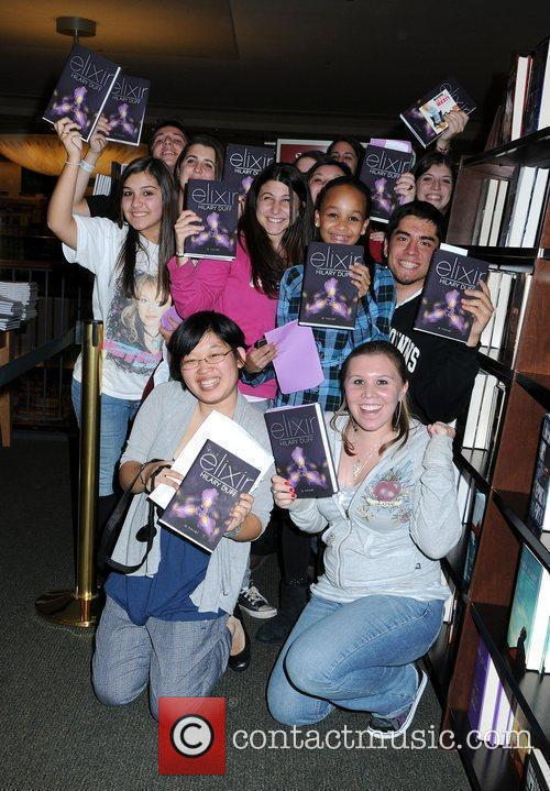 Delighted fans hold copies of Hilary Duff's book...