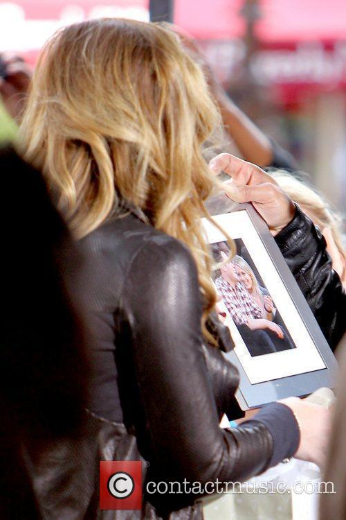 Hilary Duff receives a framed photo as a...