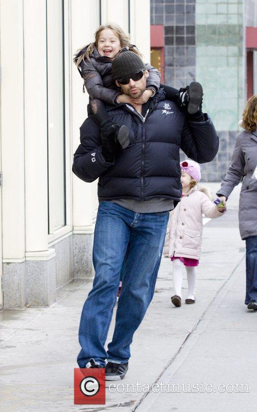 Carries his daughter Ava Eliot Jackman while walking...