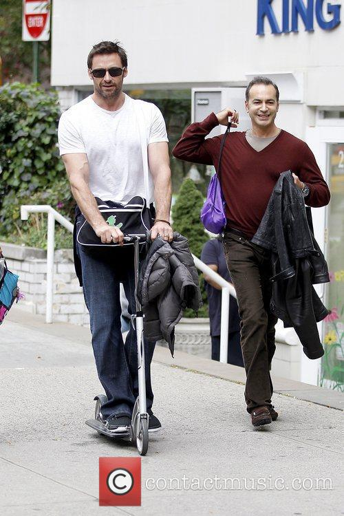 Hugh Jackman walking with a scooter as he...