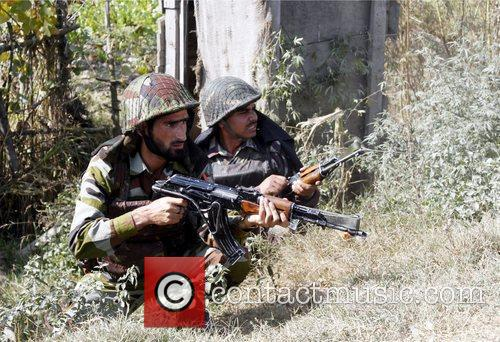 Indian soldiers take positions during an encounter as...