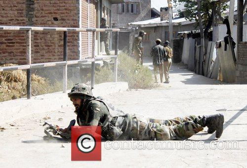 An Indian Army soldier take position as they...