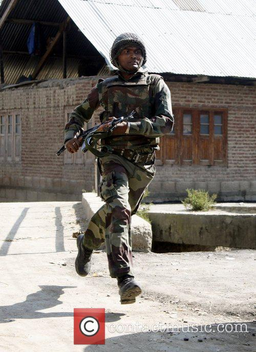 Indian Army soldier runs towards the house where...