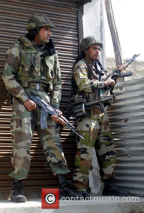 Indian Army soldiers take cover behind a wall...