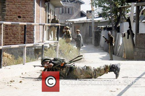 An Indian army soldier lies as he takes...