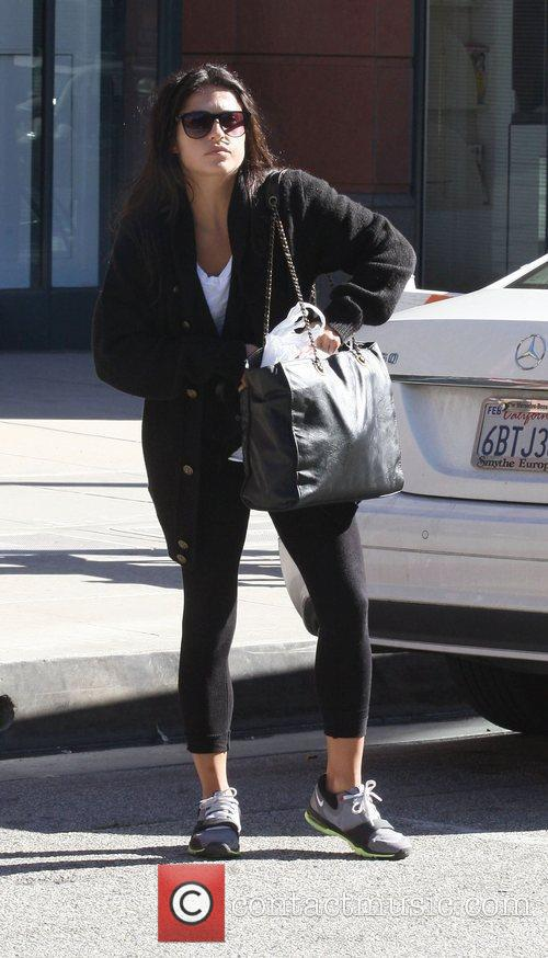 Jennifer Esposito in an oversized cardigan and carrying...