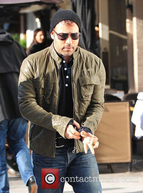 Jeremy Piven, unshaven and wearing a brown leather...