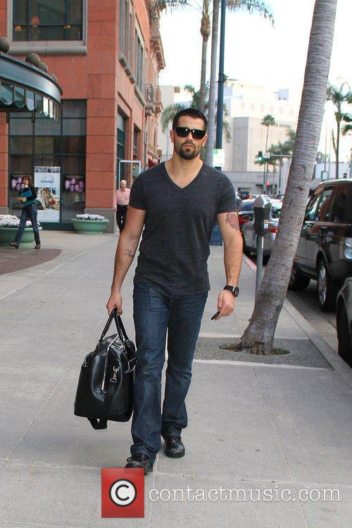 Jesse Metcalfe carries a leather duffel bag while...