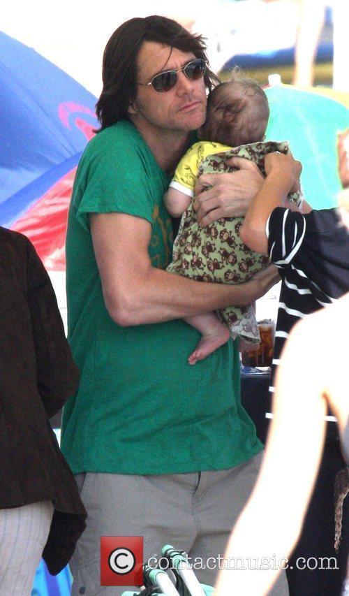 Jim Carrey holding his grandson Jackson Santan on...