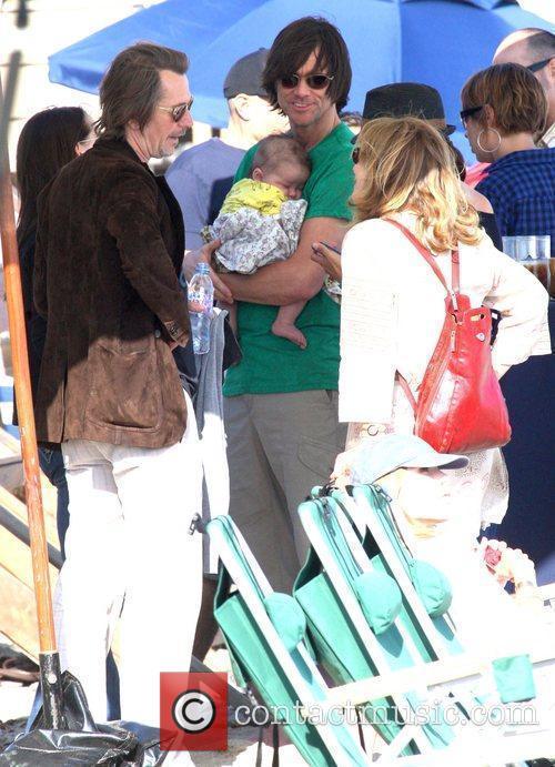Jim Carrey holding his grandson Jackson Santana while...