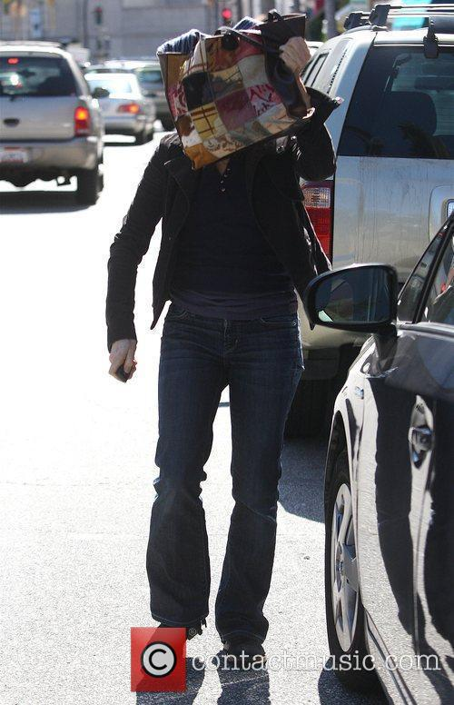 Jodie Foster covers herself with her handbag as...