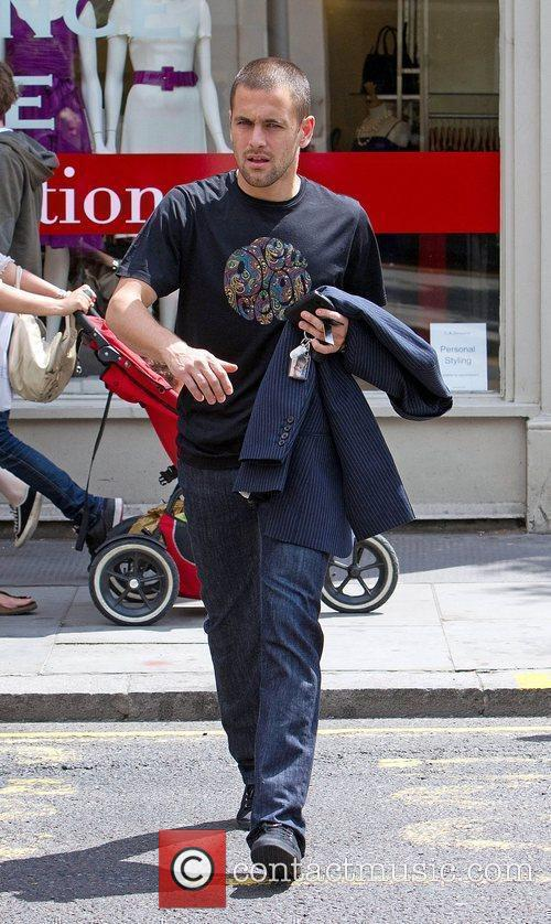 Near his London home holding a keyring featuring...