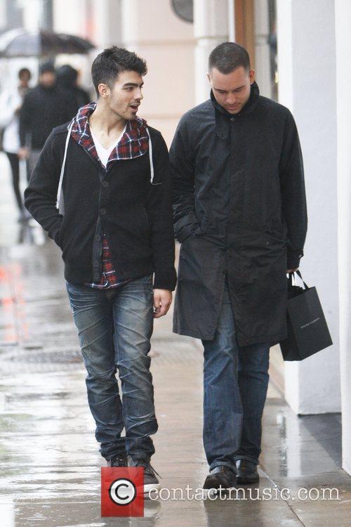Joe Jonas is seen walking in the rain...