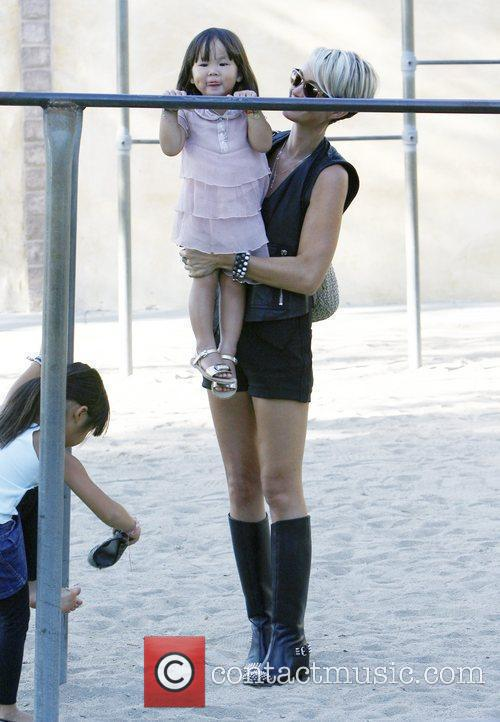 Plays with her daughter at a playground in...