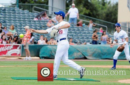 Jonas Brothers participate in a softball game to...