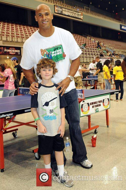 Jason Taylor with a young fan during the...