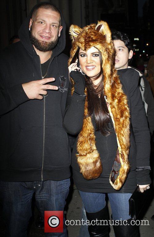 Khloe Kardashian posing with a fan as she...
