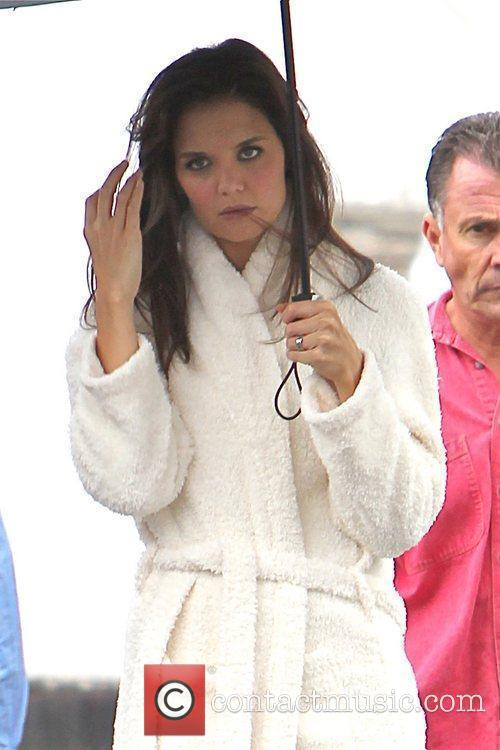 Katie Holmes shelters underneath an umbrella as she...
