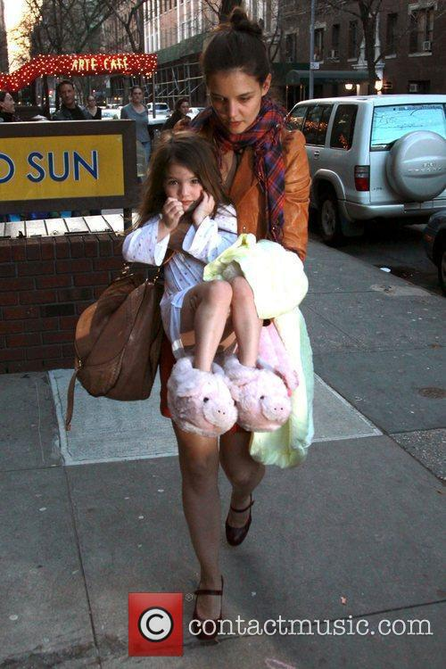 Katie Holmes carries her daughter Suri Cruise, who...