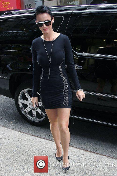 Katy Perry, wearing a studded form-fitting black dress,...